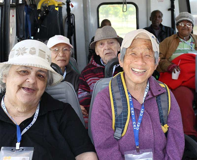 Happy seniors in a van, wearing Center for Elders' Independence badges