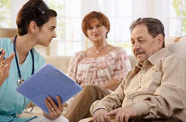 Nurse consulting with elderly man and caretaker
