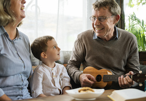 Photo of man playing ukelele for his wife and grandson