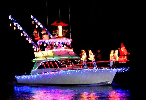 Photo of boat with many holiday lights in darkness