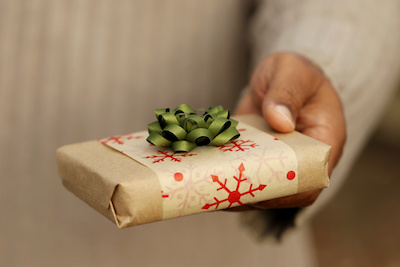 Photo of man's hand offering a small gift wrapped with paper and a bow