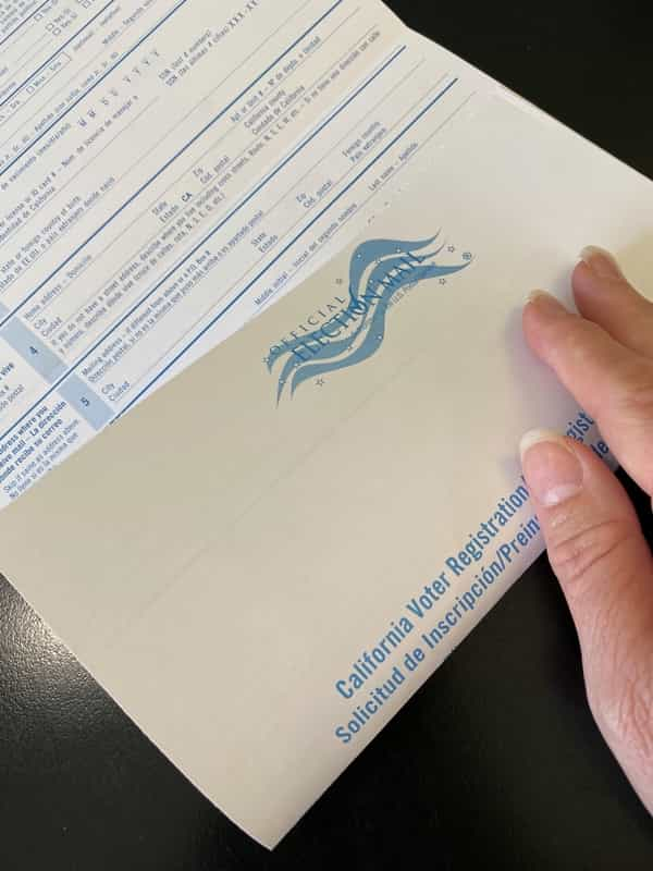 Folding the bottom half of voter registration card.