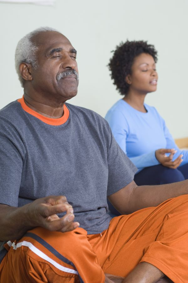 Senior man and younger woman sit in mediation
