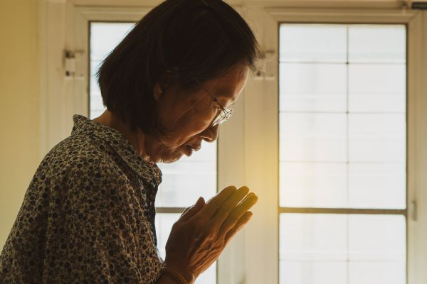 Woman bowing with prayer hands