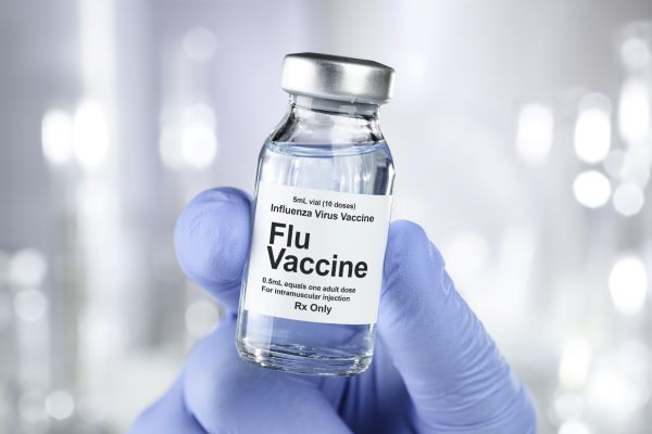 A flu vaccine bottle held up.